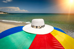 Conceptual photo of hat lying on colorful umbrella at seashore Royalty Free Stock Photography