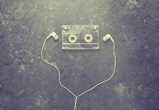 Conceptual photo illustrating the love of music. Audio cassette and headphones on a black concrete background. Top view Stock Photo