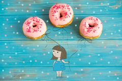 A conceptual photo of pink donuts on a blue wooden background. Hand-drawn cartoon girl holding donuts like inflatable balls
