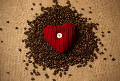 Conceptual photo of red heart lying on pile of coffee beans Stock Image