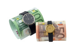 Conceptual photo - time is money. Time is money concept photo: two watches with fifty and one hundred euro banknotes, isolated on a white Royalty Free Stock Image