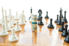 Conceptual photo of twisted money on wooden chessboard Stock Photography