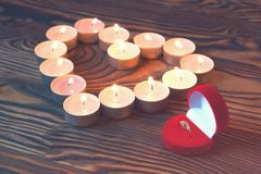 Conceptual photo of wedding ring witn candles in shape of heart Stock Photos