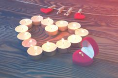 Conceptual photo of wedding ring witn candles in shape of heart Royalty Free Stock Images