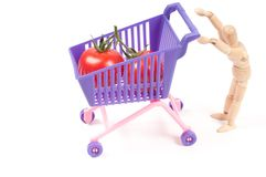 Conceptual photo with wooden man and shopping-cart Royalty Free Stock Image