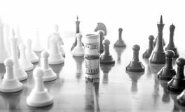 Conceptual photo of wrapped money playing in chess as chess piec Stock Photo