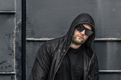 Conceptual photo of young and serious rapper in black zipped jacket. Stock Photos