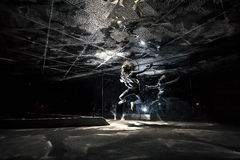 Conceptual photo of young woman jumping at night around mirror walls and top. Stock Image