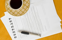 Conceptual photograph of contract signing. The form of the contract with a pen and a Cup of black coffee standing on a wooden surface stock photo