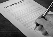 Conceptual photograph of contract signing. The form of the contract with a pen stand on wooden surfaces (black and white stock photos