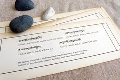 Studying Tibetan buddhism scriptures. A conceptual photograph showing some tibetan language buddhist sutra scriptures on natural linen cotton background with a Royalty Free Stock Image