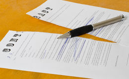 Conceptual photography of the cancellation of the contract. Broken e contract with a pen lying on a wooden surface Stock Image