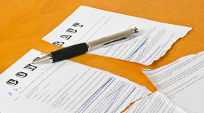 Conceptual photography of the cancellation of the contract. Broken contract  with a pen lying on a wooden surface Stock Photography