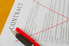 Conceptual photography of the cancellation of the contract. Crossed the red lines of the contract with a pen lying on a wooden surface Royalty Free Stock Image