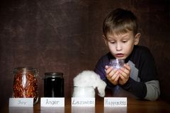 European appearance boy. In jars next to him joy, anger, laziness. In the hands of a child a jar of happiness royalty free stock image