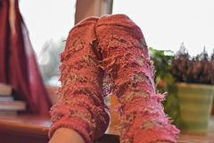 Female feet in pink woolen socks by the window, retro style tonal correction photo filter Royalty Free Stock Image