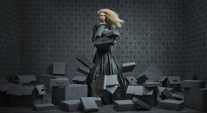Conceptual picture of a blond lady among a lot of boxes. Conceptual picture of a blond lady among a lot of paper boxes Stock Photos