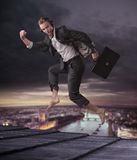 Conceptual picture of a businessman jumping on the top of a skys Royalty Free Stock Images