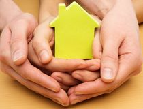 Conceptual picture of a little house. Man and woman hands holding conceptual paper house Royalty Free Stock Images