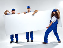 Conceptual picture of three crafstmen holding an empty board. Conceptual picture of three crafstmen holding an empty, white board royalty free stock images
