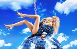 Conceptual picture of a lady swinging on disco ball royalty free stock images