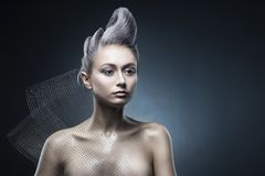 Conceptual portrait of beautiful naked shoulders vanguard hairstyle metallic colour hair girl wearing steel construction armature. Mesh. Copy space. Building stock images