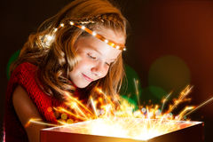 Conceptual portrait of cute girl staring at light box. Royalty Free Stock Image