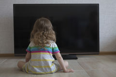Conceptual portrait. Little girl laying on the floor and watching TV at home. Little girl is sitting on the black screen of the TV Royalty Free Stock Photos