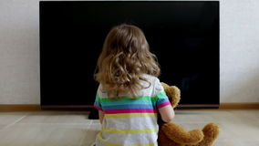 Conceptual portrait. Little girl is sitting on the floor against the black screen of the TV set stock footage
