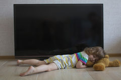 Conceptual portrait little girl is sleeping on the floor on the background of a black TV screen Stock Photography