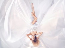 Conceptual portrait of a prety blonde wearing white sheet dress Royalty Free Stock Photos