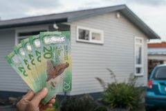 Cropped shot view of men hand holding New Zealand dollar bills in front of a single house in New Zealand. Conceptual of Real estate business. New Zealand dollar stock images