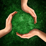 Conceptual Recycling Symbol. Made from hands on abstract grungy green background Stock Photo