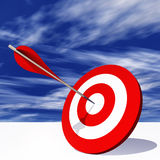 Conceptual red dart target board with arrow in the center on clouds Royalty Free Stock Photos