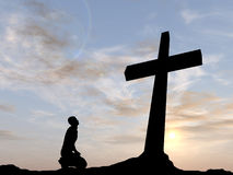 Conceptual religion cross with a man at sunset. Conceptual religion black cross with a man praying at sunset background Royalty Free Stock Images