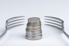 Conceptual imagination of financial greed. Conceptual representation of financial greed by two forks and coins Stock Photography
