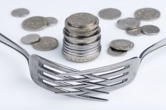 Conceptual imagination of financial greed. Conceptual representation of financial greed by two forks and coins Stock Images