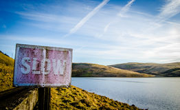 Conceptual Scenic Slow Sign. Conceptual Image Of Rustic Slow Sign Beside Tranquil Scenic Lake Royalty Free Stock Images