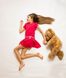 Conceptual shot of cute happy girl running with teddy bear Royalty Free Stock Photos