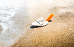 Conceptual shot of flip flops and sunblock lotion on sandy beach Stock Photography