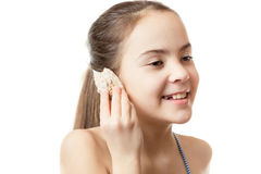 Conceptual shot of girl listening to ocean in the shell Royalty Free Stock Photography
