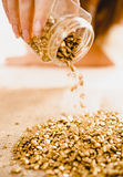 Conceptual shot of hand turning over bullion with golden nuggets Royalty Free Stock Photo