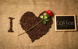 Conceptual shot of I love coffee spelled by coffee. Beans, chalk board and red rose Stock Photography