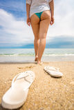 Conceptual shot of woman taking of shoes and walking in the sea Royalty Free Stock Images