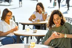 Conceptual smart phone obsession among young adults. Close up portrait of three young female students sitting with smartphones on terrace in city. Conceptual royalty free stock photos
