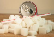 Conceptual still life image of pile of sugar cubes and soda refresh drink with straw in unhealthy nutrition sugar addiction and re stock photos