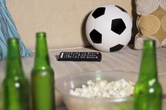 Conceptual watching football game at sofa on television with beer bottles and popcorn bowl in friends enjoying soccer game TV. Conceptual still life no people Stock Photography