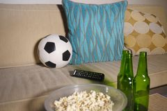 Conceptual watching football game at sofa on television with beer bottles and popcorn bowl in friends enjoying soccer game TV. Conceptual still life no people Royalty Free Stock Photography