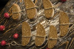 Conceptual still life photography of pieces of bread tied with t. Wine, lying on ancient wooden table made of rough boards among several red radishes. Bakery Royalty Free Stock Photos