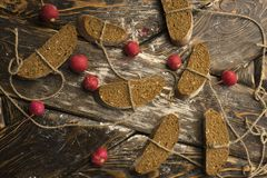 Conceptual still life photography of pieces of bread tied with t. Wine, lying on ancient wooden table made of rough boards among several red radishes. Bakery Royalty Free Stock Images